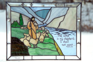 Stained glass with picture of shepherd and bible verse