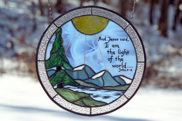 Stained glass panel with sunrise and bible verse